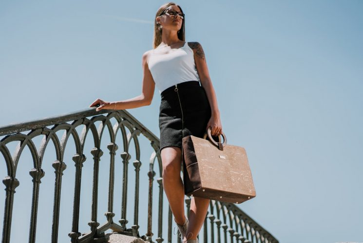 Bossy business bag in gold-natural and brown cork, carried by a women dressed in black and white, walking down stairs in front of the blue sky