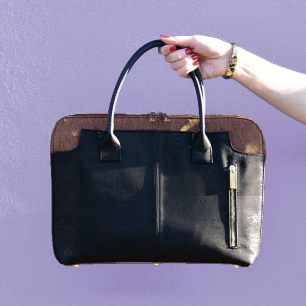 Sac business en liège noir et marron, tenu par une main devant un mur violet