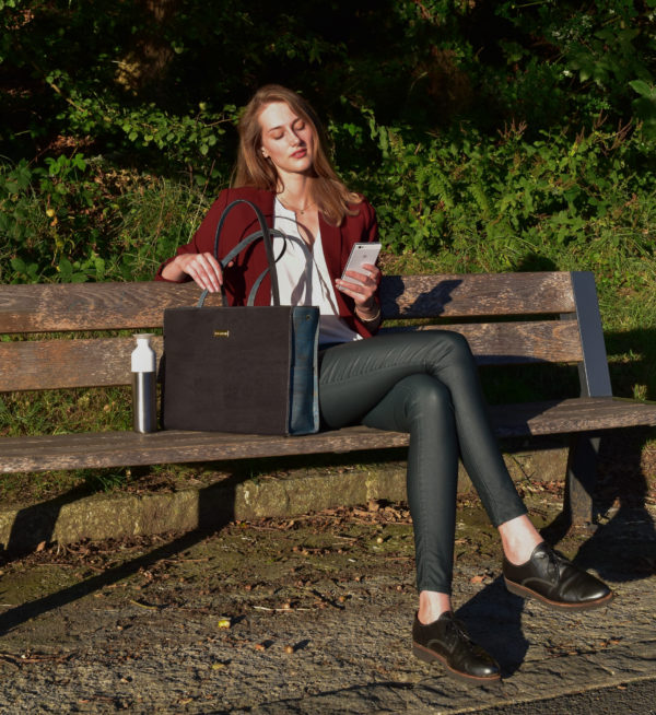 Modèle sur un banc dans la nature avec un sac d'affaires Classy en noir et vert à gauche d'elle