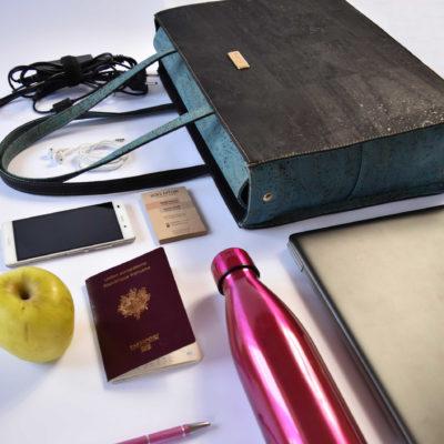 Sac d'affaires Classy avec un contenu de sac comme un ordinateur, une bouteille, un téléphone, un stylo, une pomme, un passeport et un chargeur
