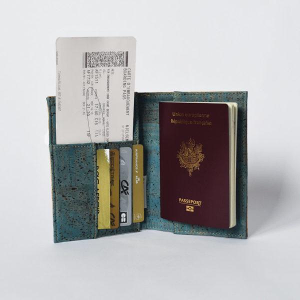 Porte passeport vue ouverte, côté vert en liège, tenant un passeport, carte d'embarquement et cartes, fond blanc