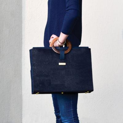 Sac d'affaires Bossy porté sur le poignet d'un modèle, vue de profil
