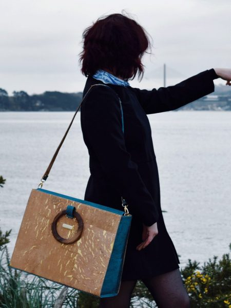 Sac d'affaires en liège vert Bossy porté avec la bandoulière bicolore sur l'épaule d'une fille qui s'habille en noir et qui pointe du doigt l'océan