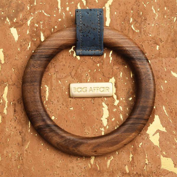 Zoom sur poignée ronde en bois de noyer brun avec étiquette en métal doré de sac à main Bossy de Bag Affair