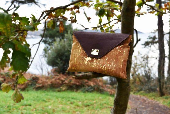 Sassy sac d'affaires en liège brun naturel et doré posé sur une branche d'arbre face à la nature et à l'océan