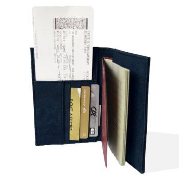 Vue ouverte de la couverture du passeport en liège noir et marine, intérieur rempli de passeport, carte d'embarquement et cartes