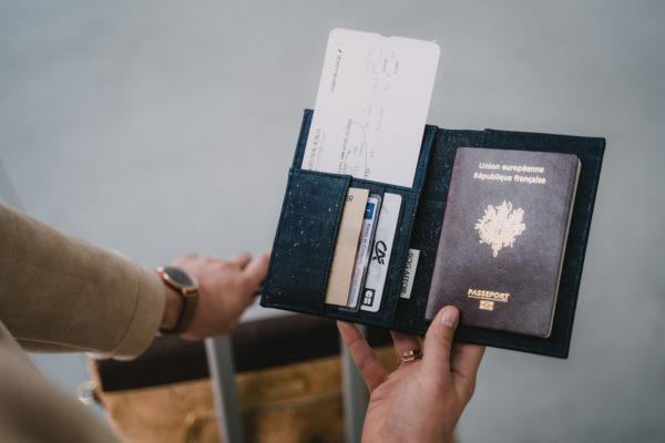 Vue de mise au point sur la couverture de passeport en liège noir-marine, tenue au-dessus d'un bagage