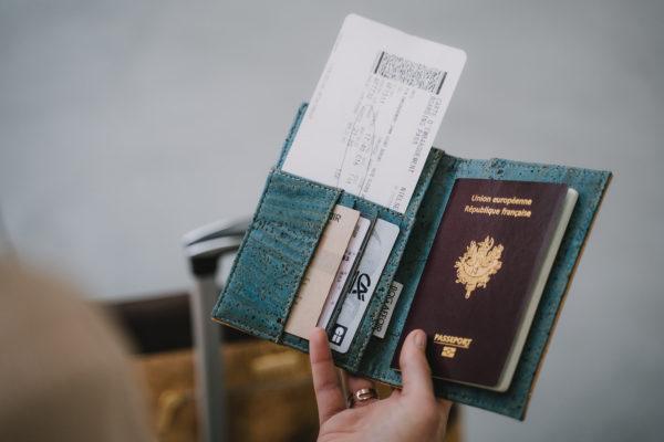 Vue ouverte de la couverture du passeport remplie, tenue au-dessus des bagages, transportant un sac d'affaires Sassy